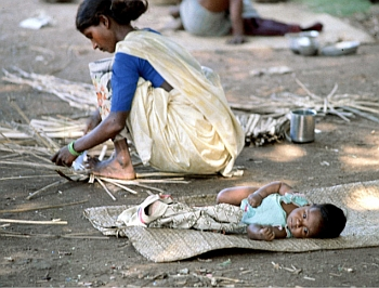 A basket weaver at work with her baby at her side, in Tamil Nadu. The infant mortality rate is very high for working women, particularly those in the primary sector, a large proportion of whom are labourers.